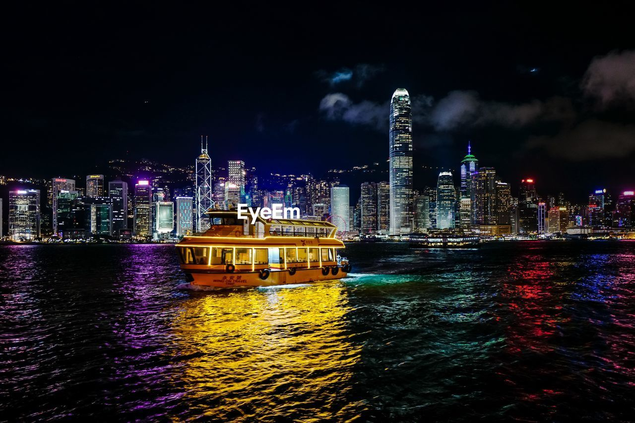 built structure, architecture, building exterior, city, night, water, illuminated, waterfront, sky, cityscape, building, nautical vessel, skyscraper, office building exterior, transportation, sea, tall - high, no people, urban skyline, outdoors, modern, financial district, passenger craft, nightlife