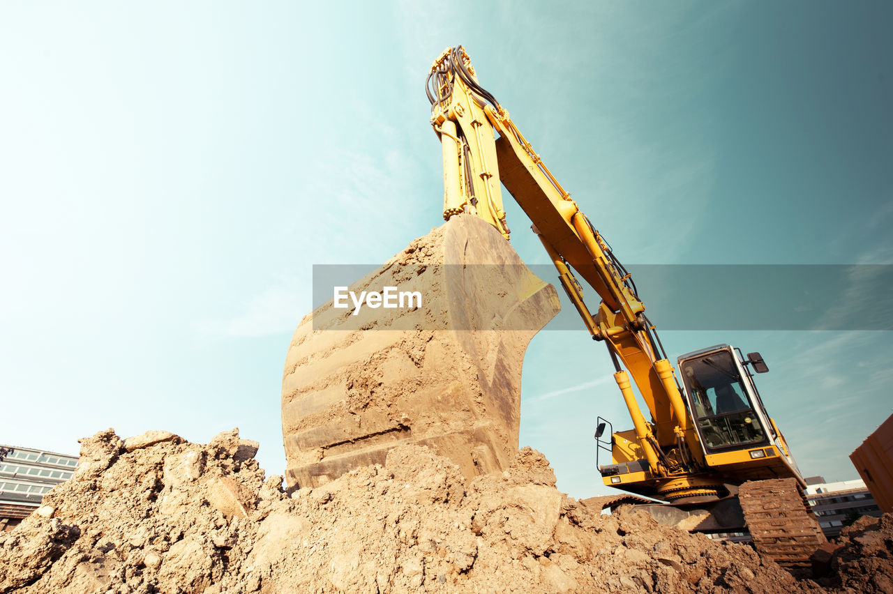 construction industry, industry, construction machinery, machinery, sky, construction site, earth mover, bulldozer, development, nature, day, construction vehicle, low angle view, sunlight, quarry, outdoors, digging, mode of transportation, mining, land vehicle, industrial equipment, construction equipment