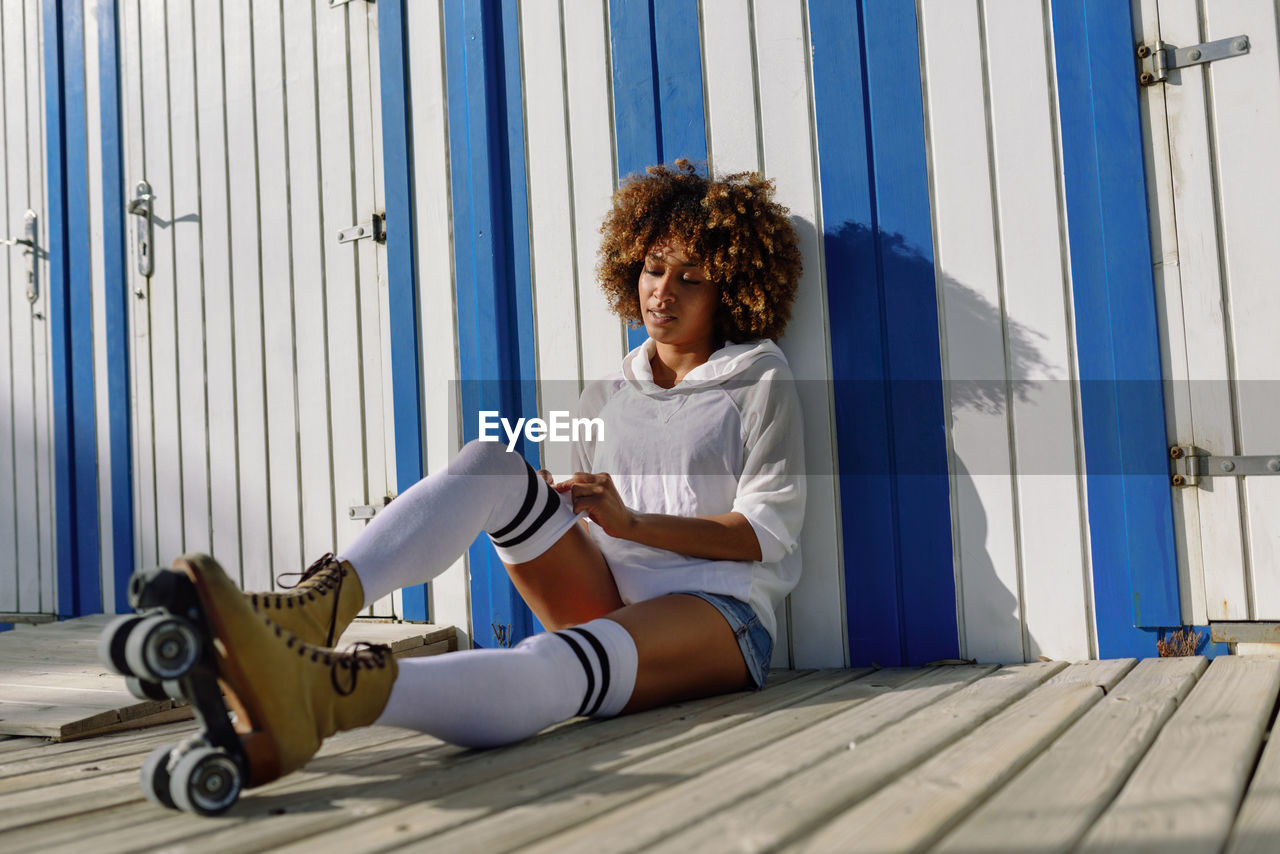 Full Length Of Young Woman With Frizzy Hair Sitting Against Building