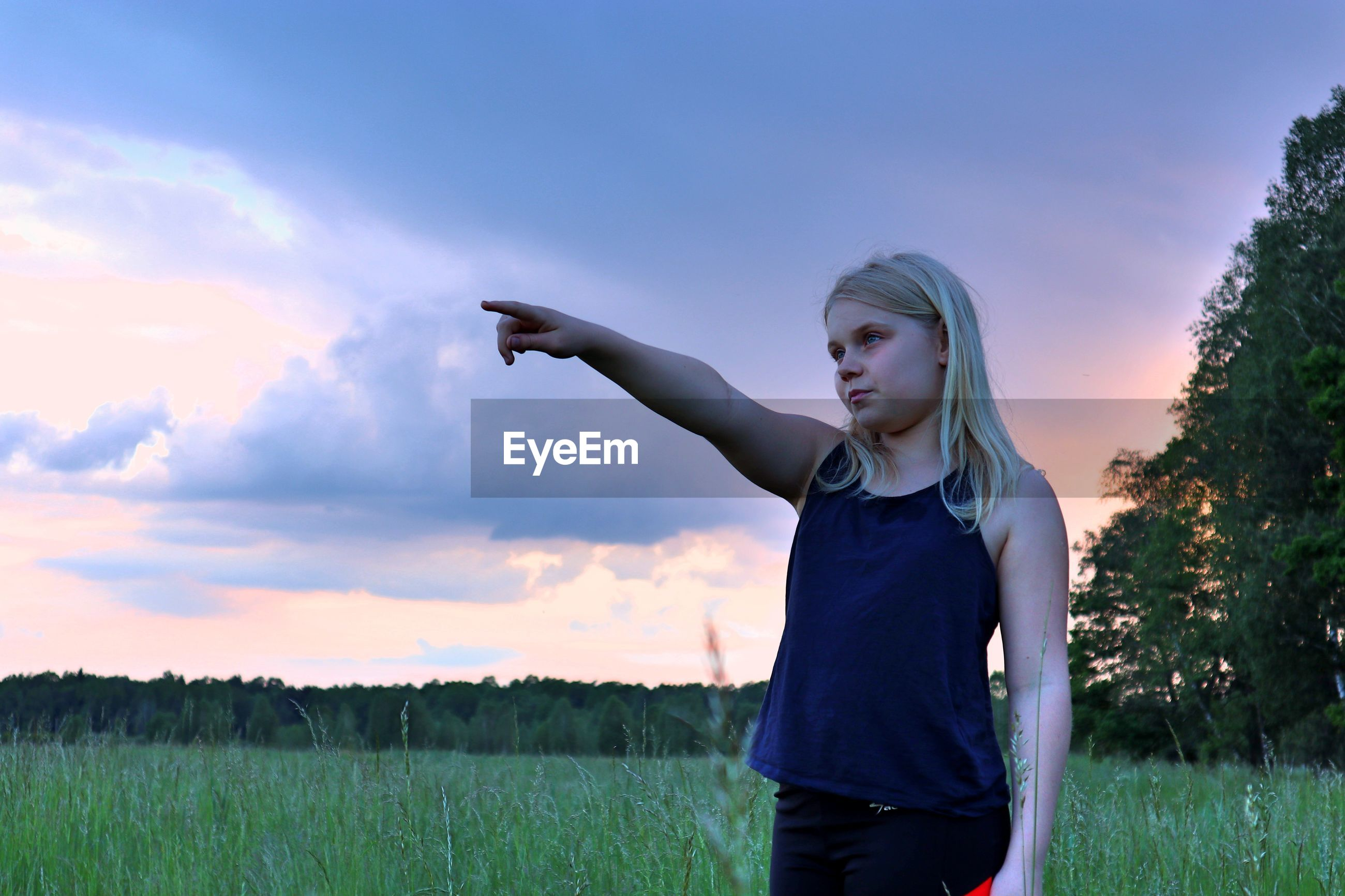 Girl pointing while standing on field against sky at sunset