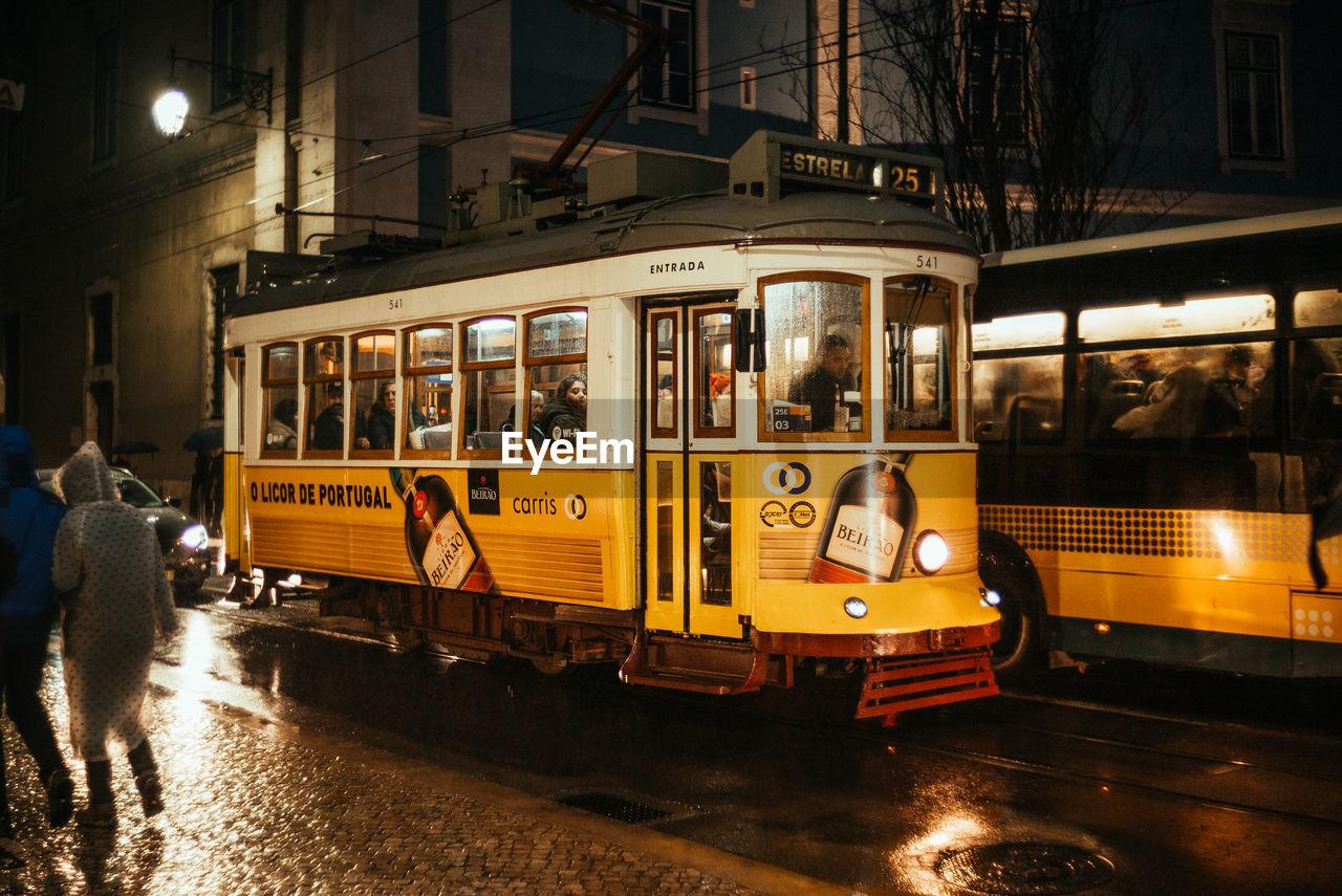 TRAIN ON STREET AT NIGHT