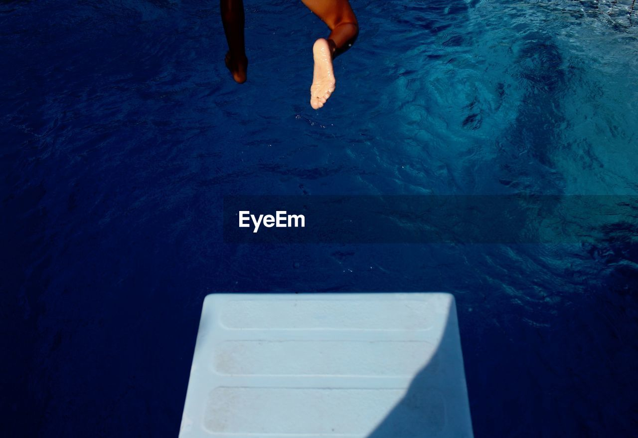 Low Section Of Man Jumping Into Swimming Pool