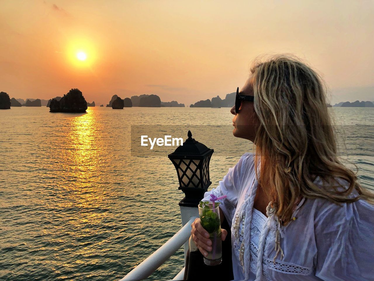 Woman having drink while looking at sea