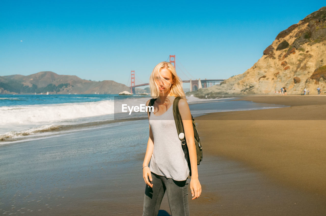 Portrait Of Woman On Shore With Golden Gate Bridge Against Clear Sky