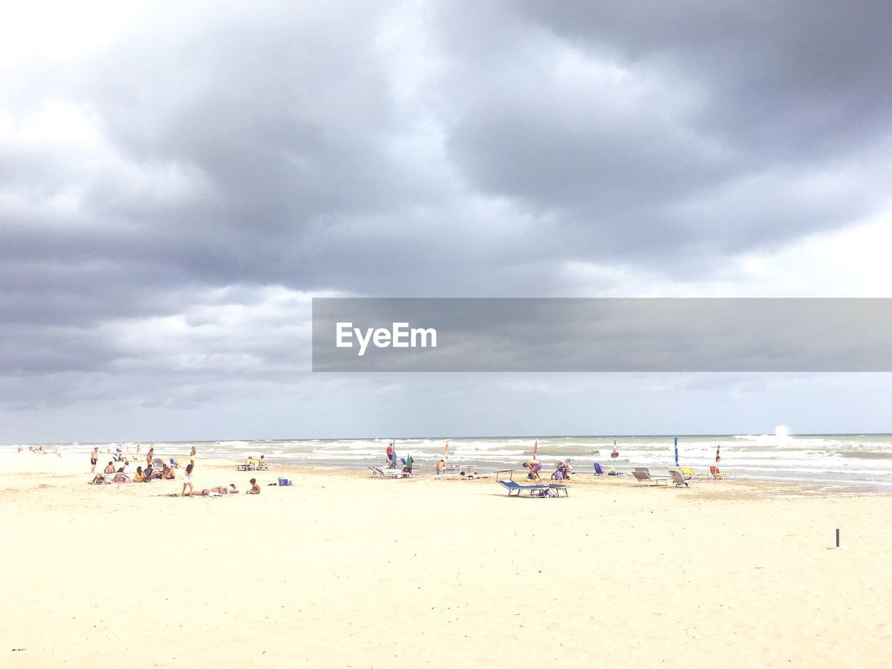 PANORAMIC VIEW OF PEOPLE AT BEACH AGAINST SKY