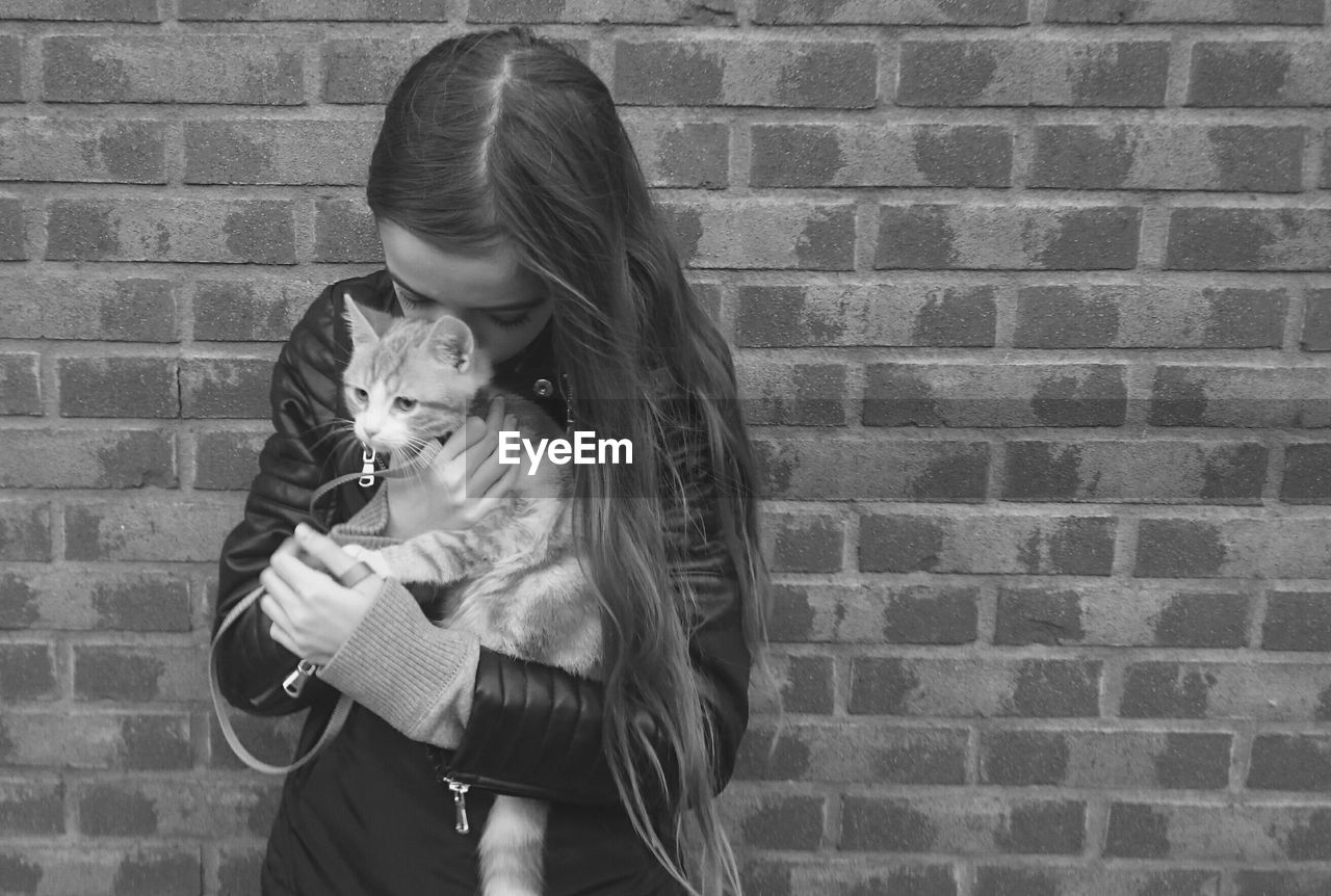 Girl embracing cat against brick wall