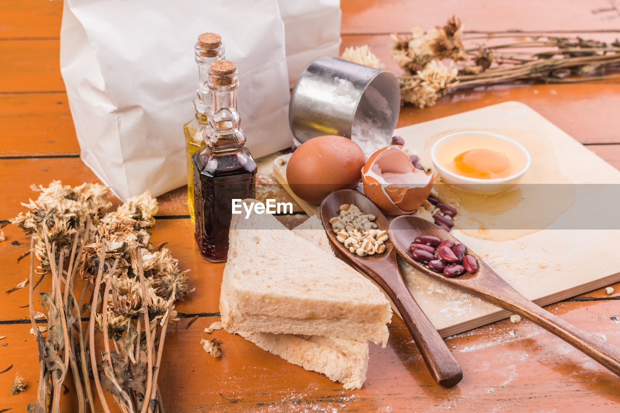 food and drink, food, table, indoors, freshness, wellbeing, still life, healthy eating, kitchen utensil, eating utensil, ingredient, no people, bread, preparation, cheese, olive oil, high angle view, oil, wood - material, spoon