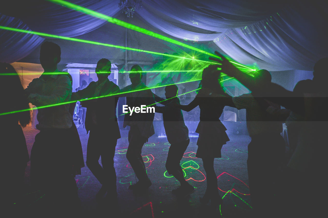 Group Of People Dancing In Nightclub During Party