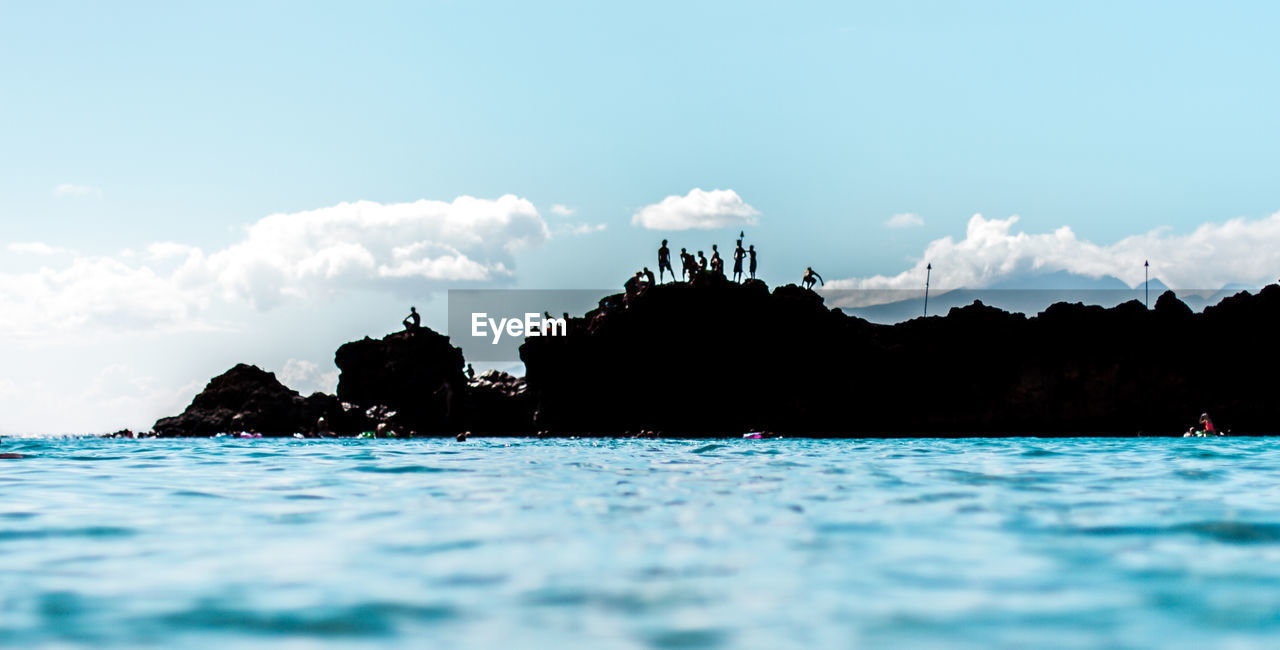 Water surface view of silhouette people standing on rocks against sky