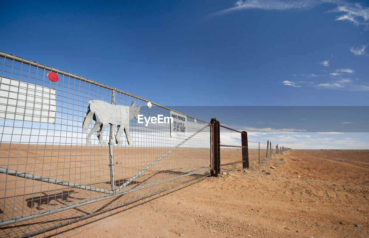 Chainlink fence on arid landscape against blue sky during sunny day