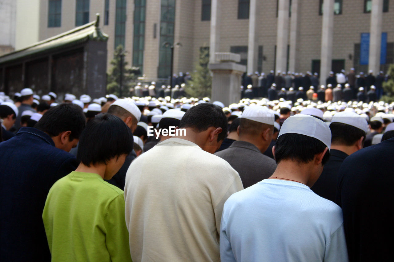 Rear view of crowds praying outside mosque