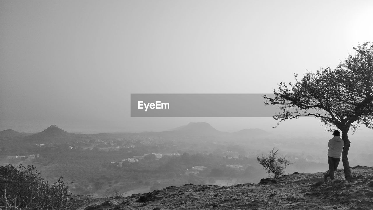 Man standing by tree on mountain peak