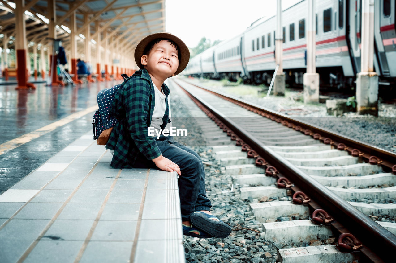 rail transportation, track, railroad track, transportation, real people, one person, mode of transportation, lifestyles, public transportation, railroad station, casual clothing, travel, leisure activity, young adult, day, train - vehicle, train, railroad station platform, outdoors
