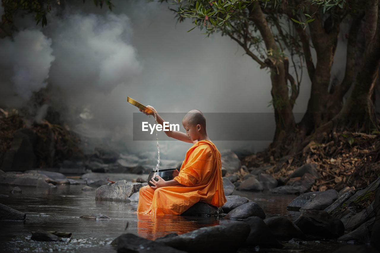 Monk Pouring Water In Container At Lake