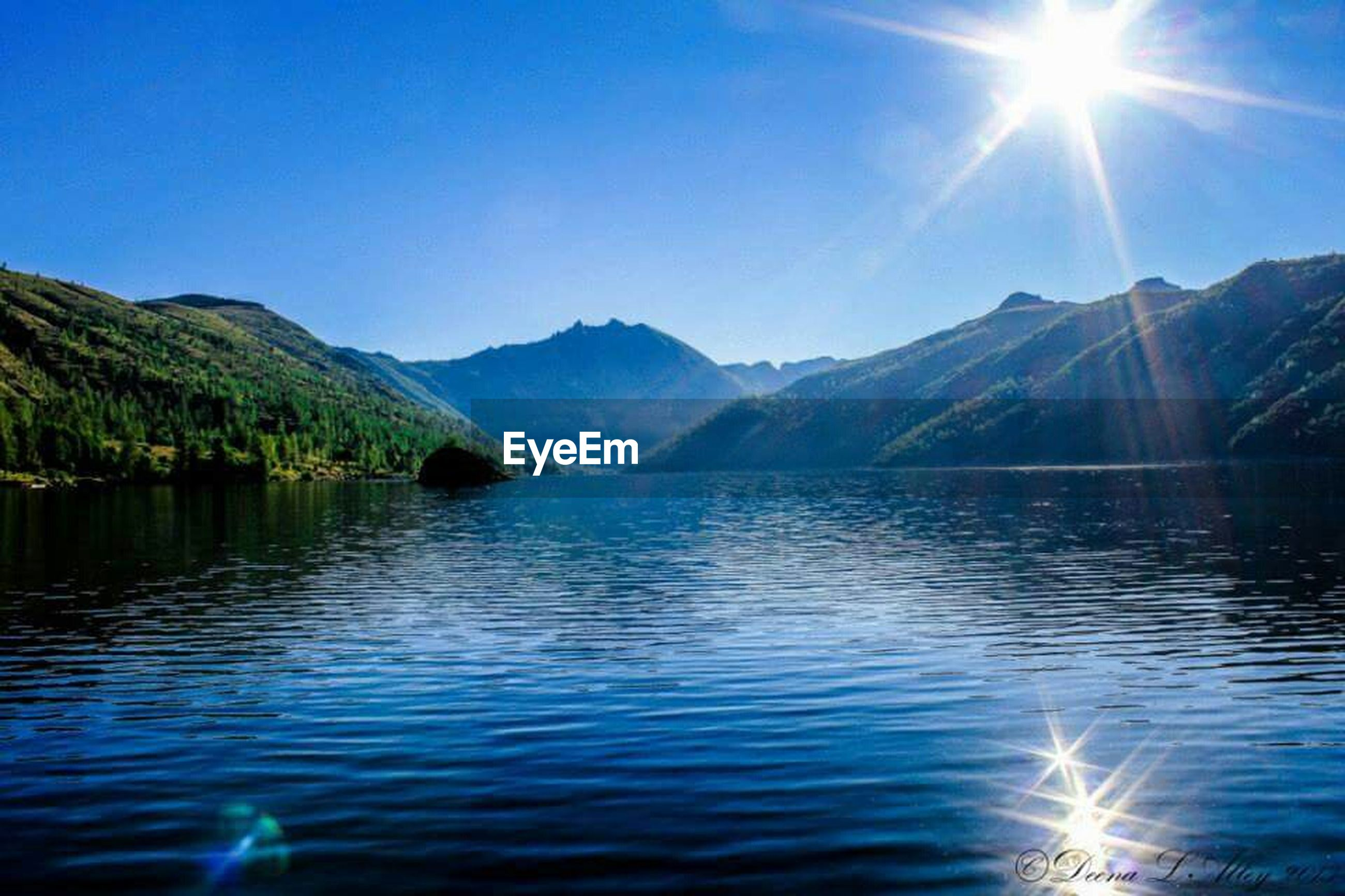 water, mountain, sun, sunbeam, sunlight, scenics, tranquil scene, beauty in nature, waterfront, tranquility, mountain range, lake, reflection, lens flare, blue, nature, clear sky, idyllic, sunny, rippled