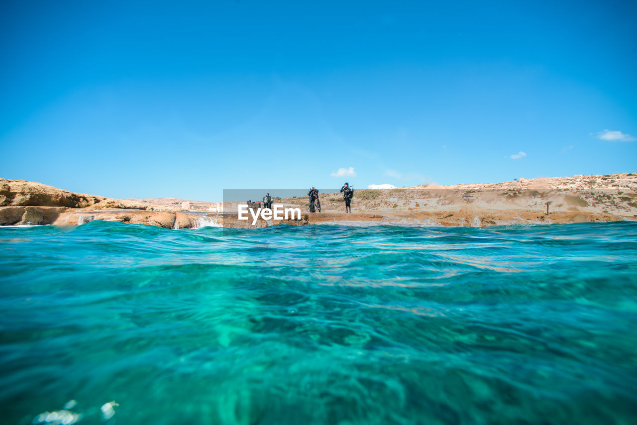 Mid distance view of scuba divers standing by sea against sky