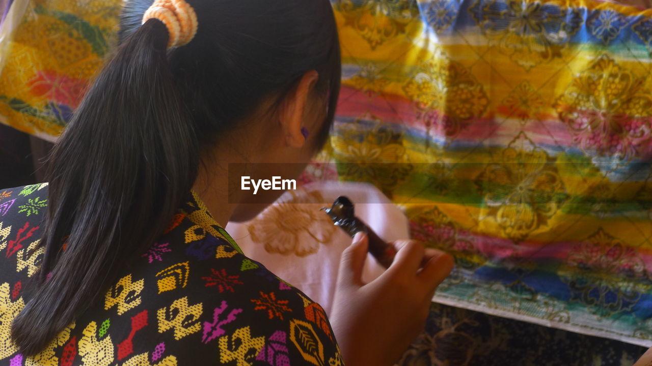 Woman applying design on fabric