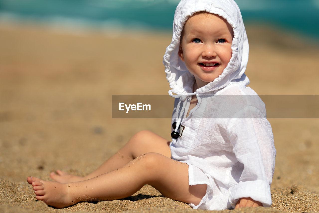 Full length of girl sitting on sand at beach