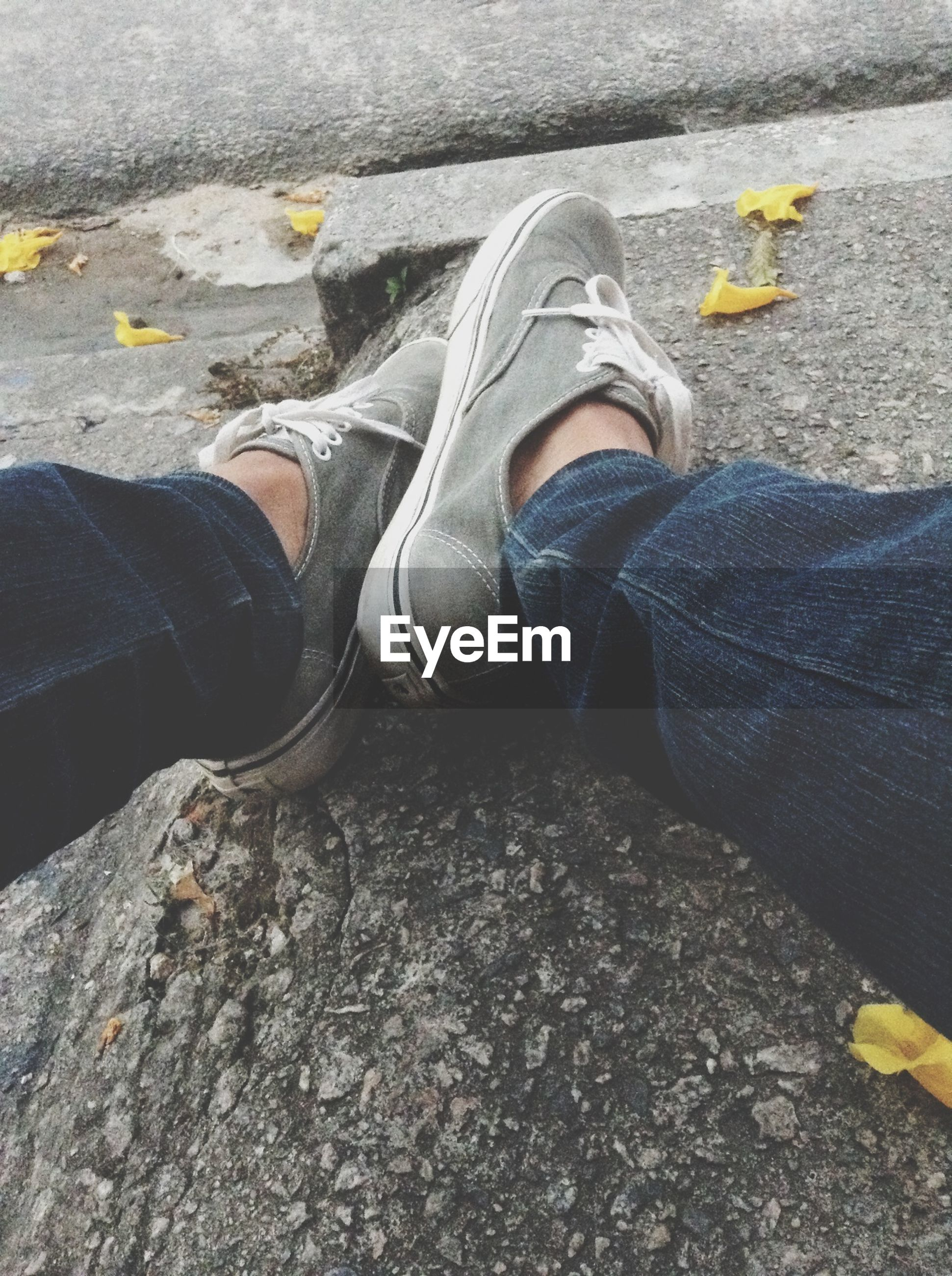 low section, person, shoe, personal perspective, jeans, footwear, high angle view, standing, lifestyles, street, human foot, men, leisure activity, yellow, canvas shoe, casual clothing, unrecognizable person