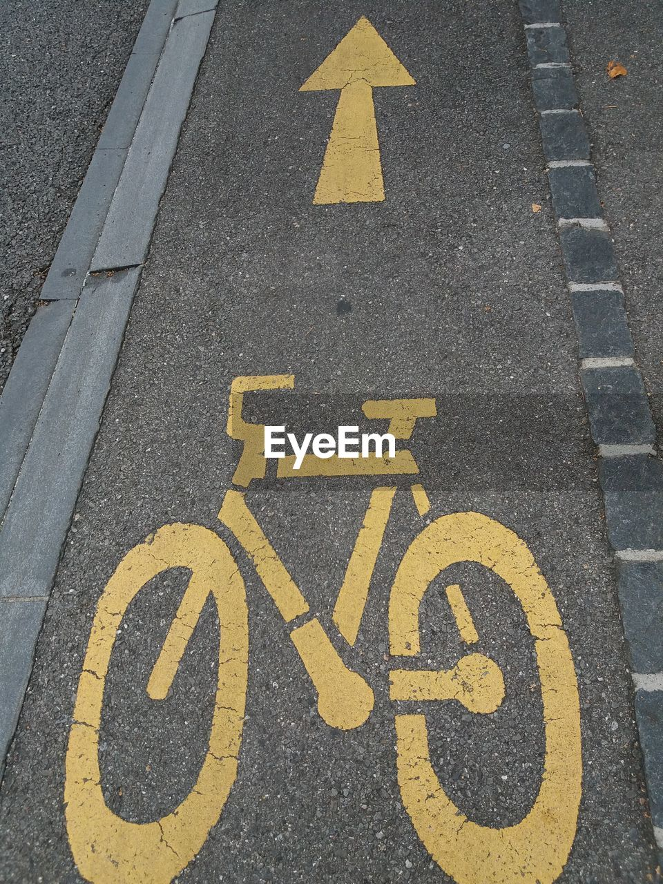 High Angle View Of Yellow Bicycle Lane Sign With Arrow Symbols On Road