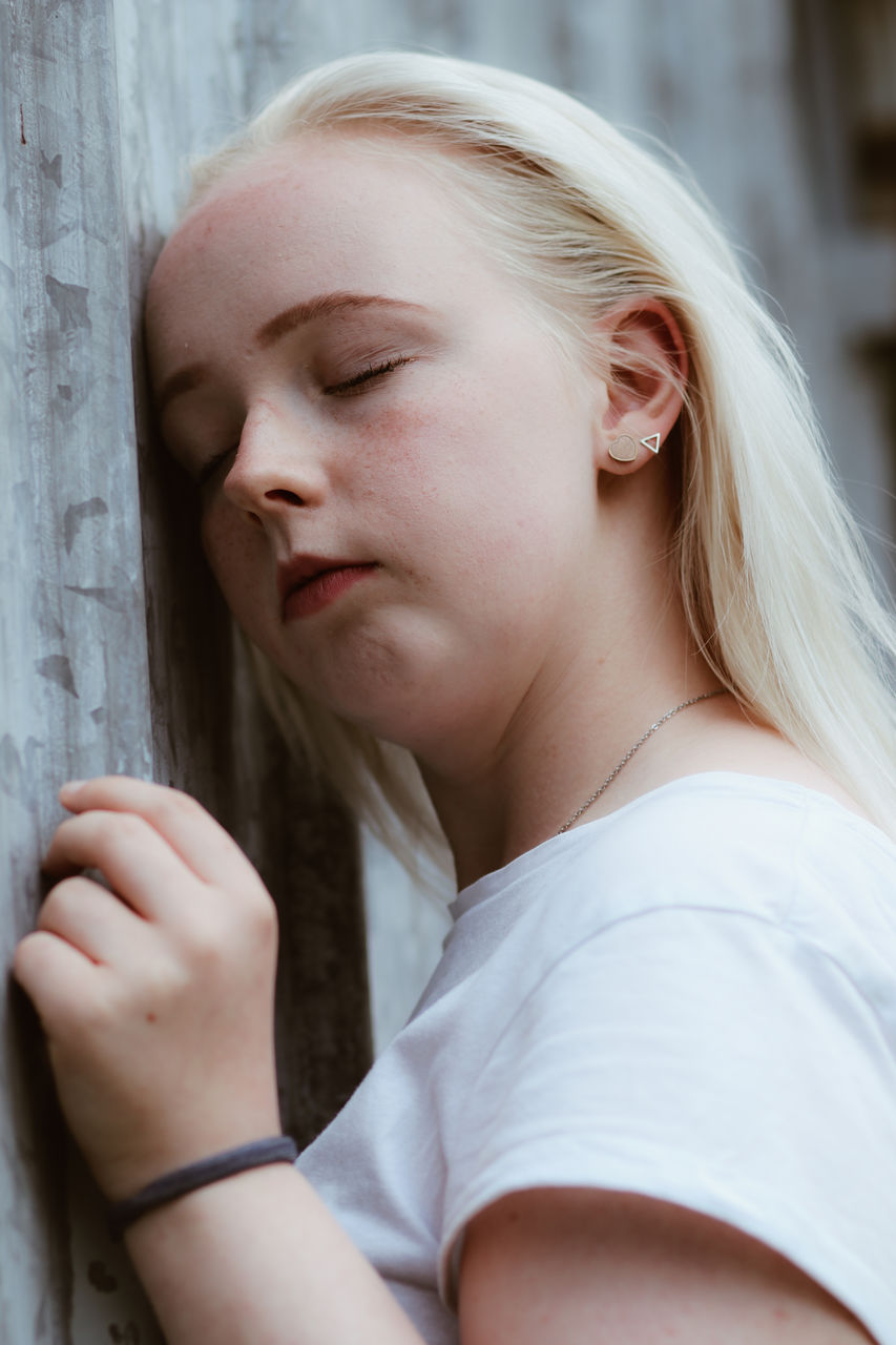 Beautiful young woman with eyes closed by wall