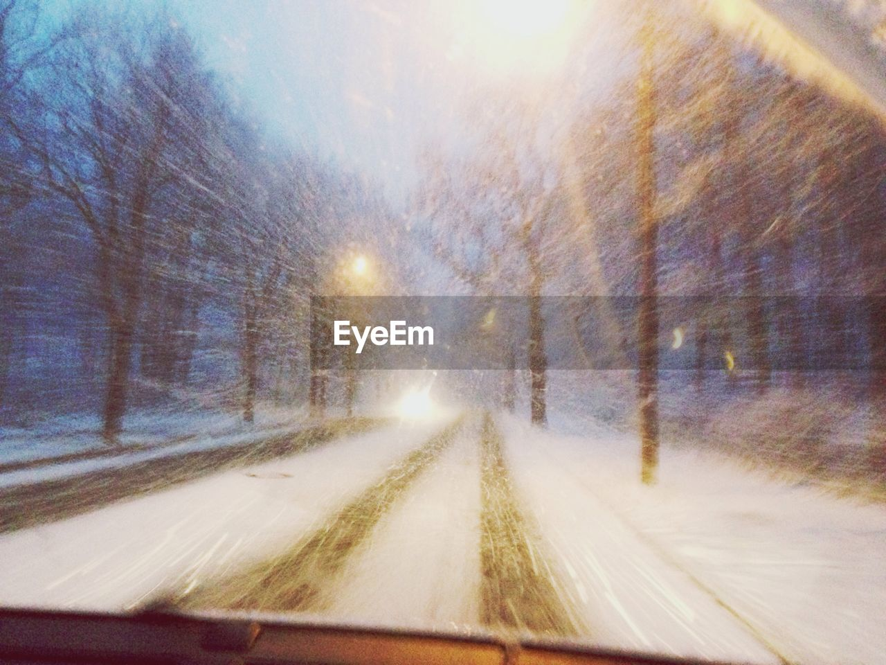 winter, cold temperature, snow, vehicle interior, windshield, transportation, weather, the way forward, no people, road, car, car interior, nature, illuminated, land vehicle, car point of view, day, outdoors, snowing, tree, beauty in nature, sky