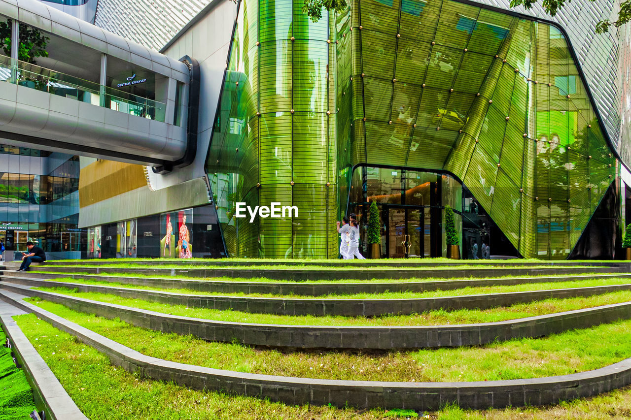 built structure, architecture, green color, building exterior, real people, men, day, adult, people, outdoors, nature, incidental people, women, lifestyles, plant, leisure activity, grass, two people, full length