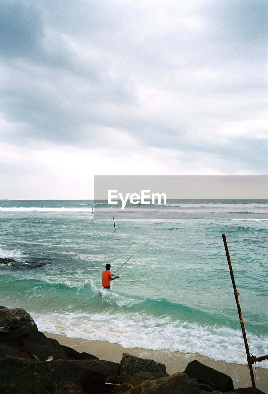 sea, horizon over water, water, sky, nature, beauty in nature, one person, scenics, tranquil scene, fishing pole, cloud - sky, tranquility, fishing, day, full length, outdoors, leisure activity, weekend activities, real people, standing, men, people