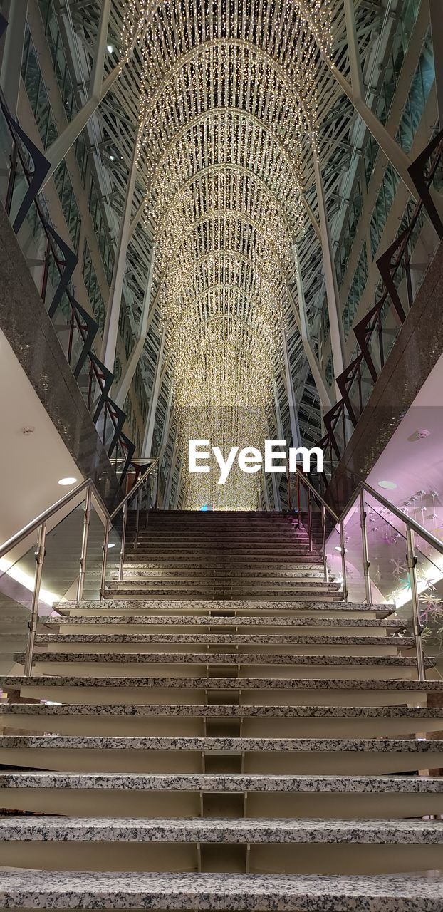 architecture, staircase, low angle view, indoors, built structure, steps and staircases, pattern, ceiling, metal, no people, railing, the way forward, illuminated, direction, arch, travel destinations, design, travel, transportation, architecture and art, ornate
