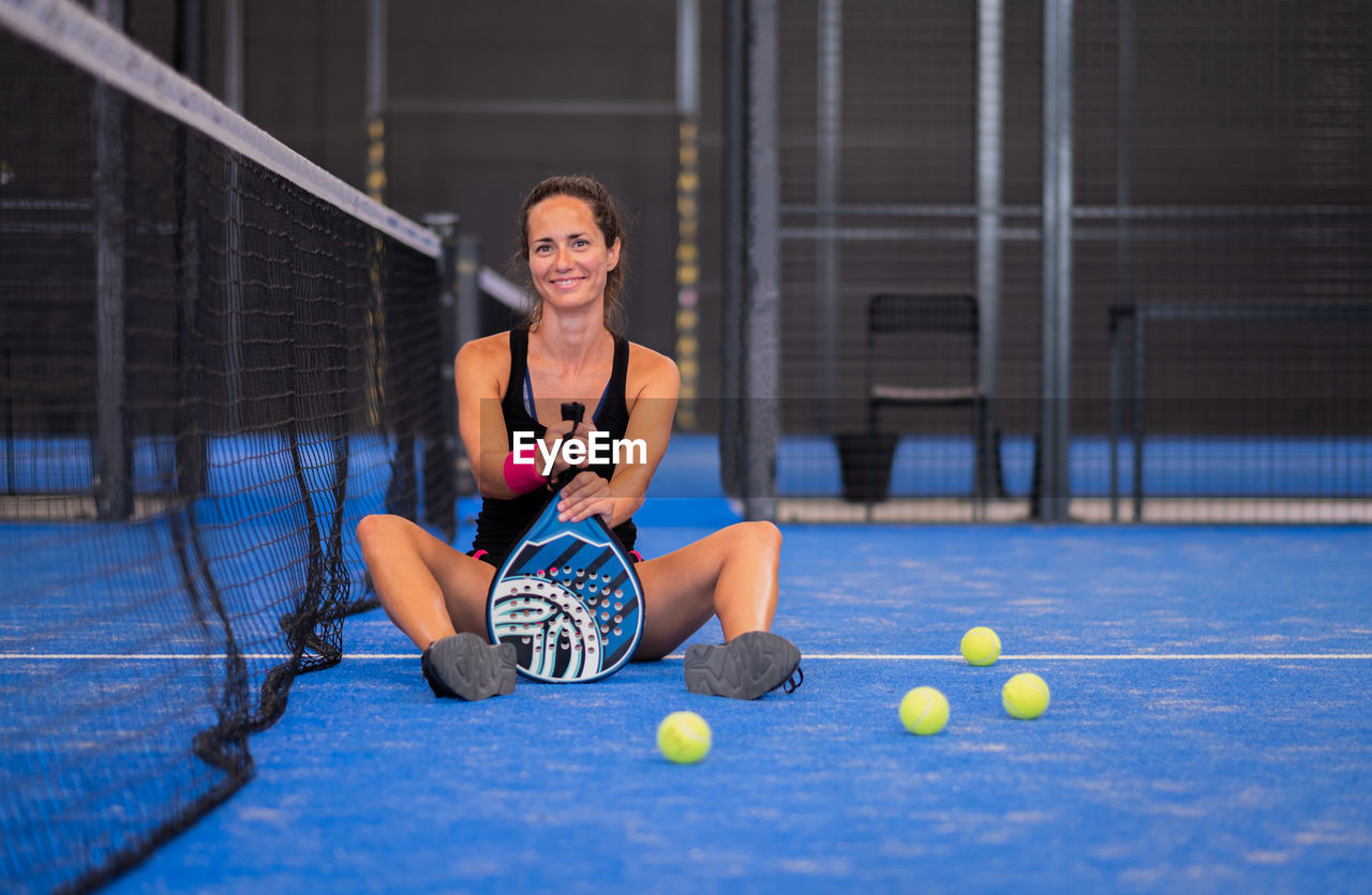 PORTRAIT OF SMILING WOMAN PLAYING WITH BALL IN BACKGROUND
