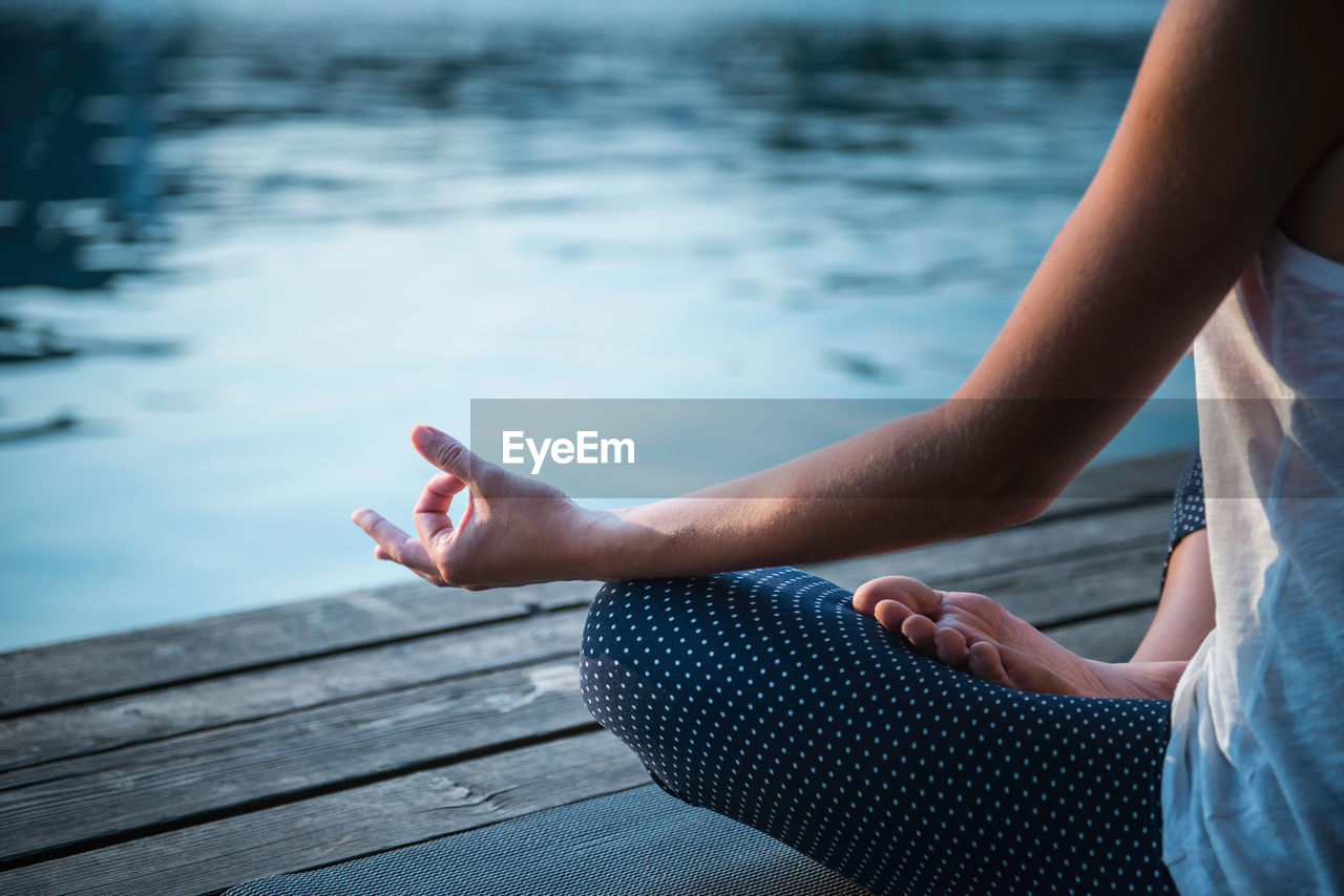 Low Section Of Woman Practicing Yoga On Pier Over Lake