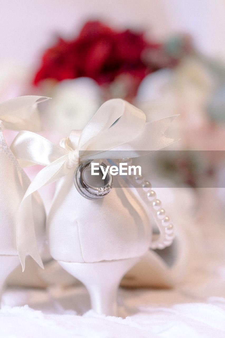 flower, celebration, jewelry, flowering plant, plant, close-up, rose, love, rose - flower, ribbon, focus on foreground, wedding, event, ring, no people, ribbon - sewing item, white color, decoration, life events, indoors, positive emotion, flower head, flower arrangement, bouquet, pearl jewelry