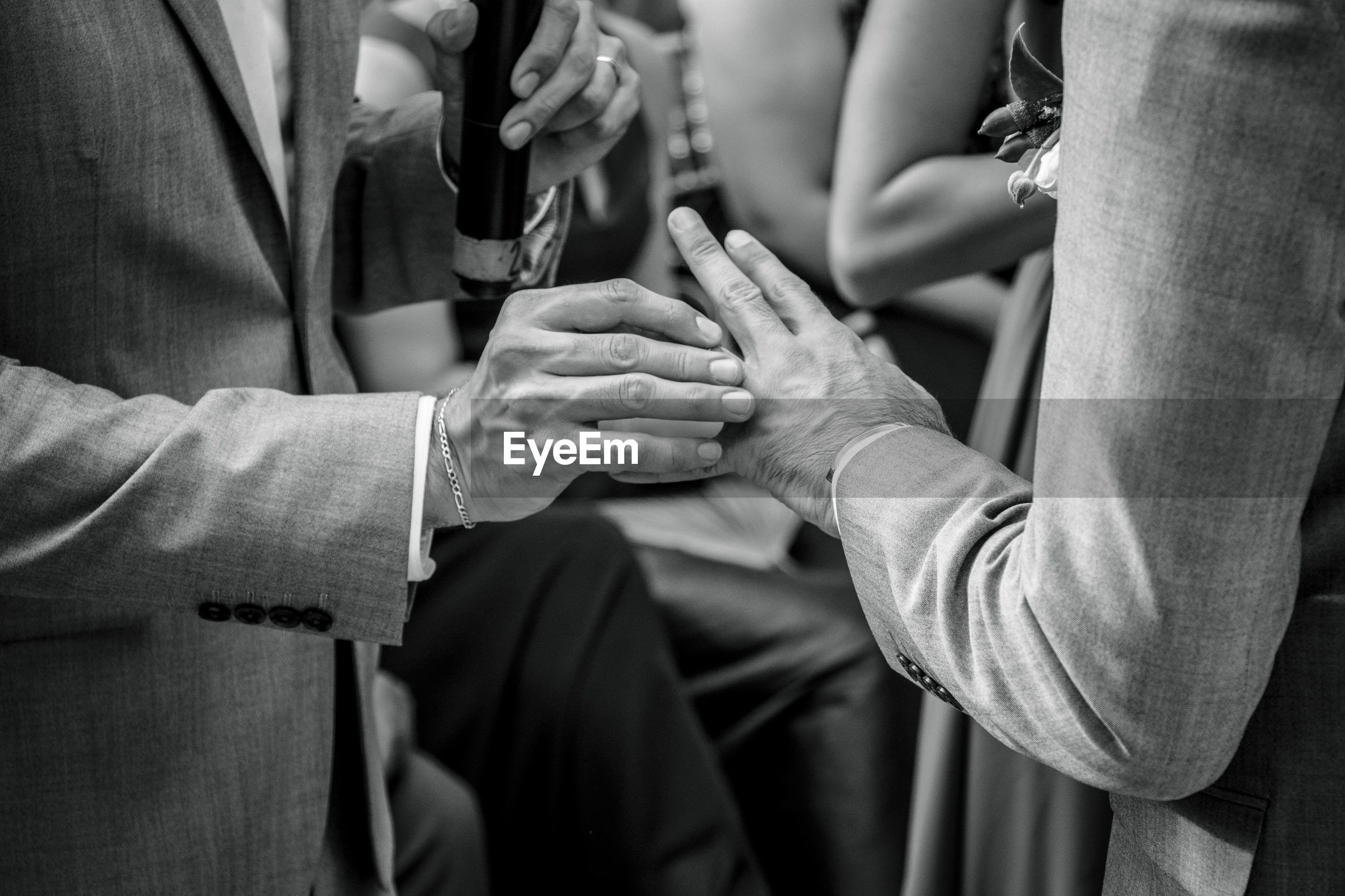 Midsection of gay couple during wedding ceremony