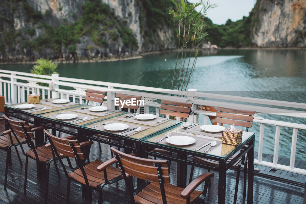Place setting at restaurant against lake