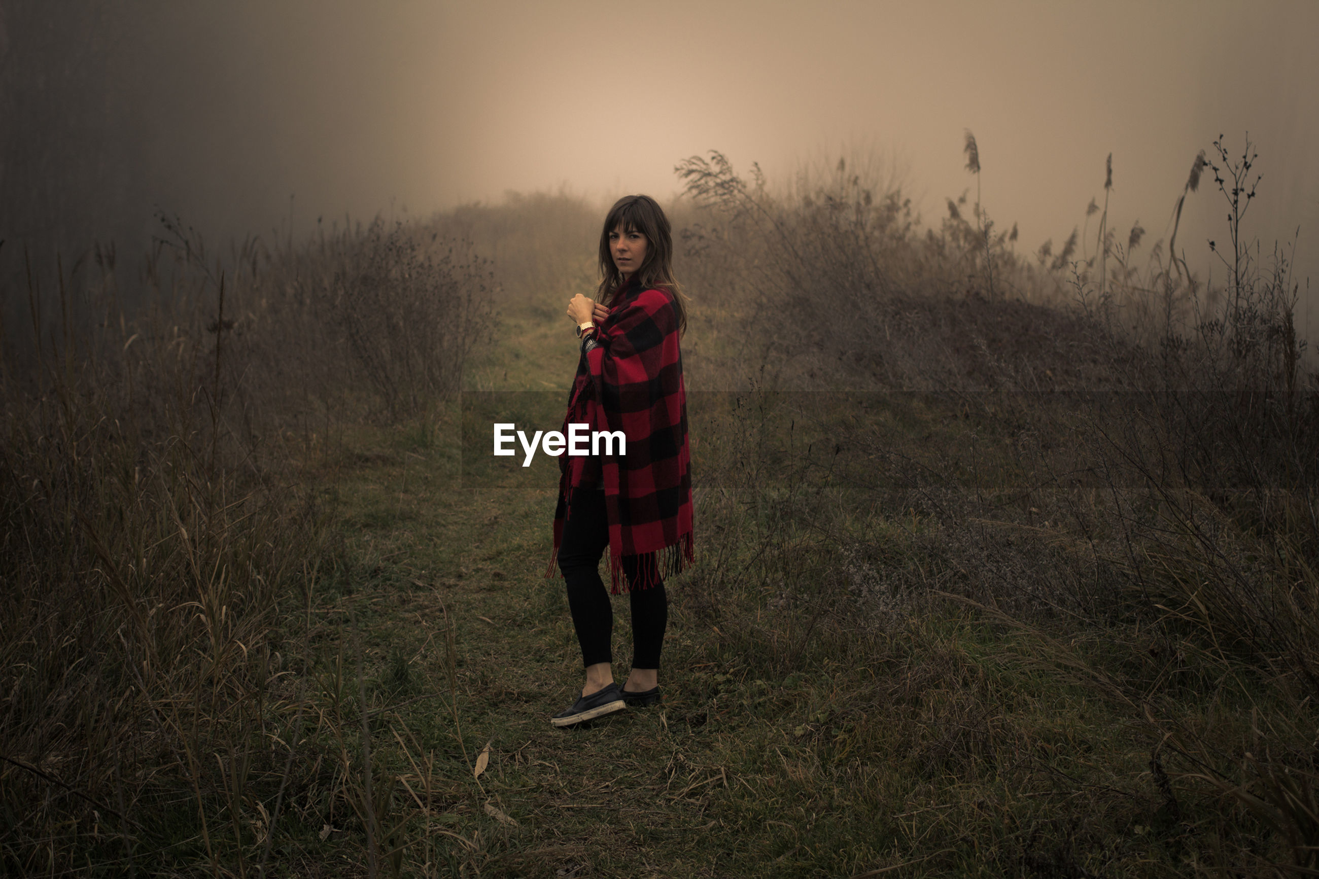 Young woman standing on grassy field during foggy weather