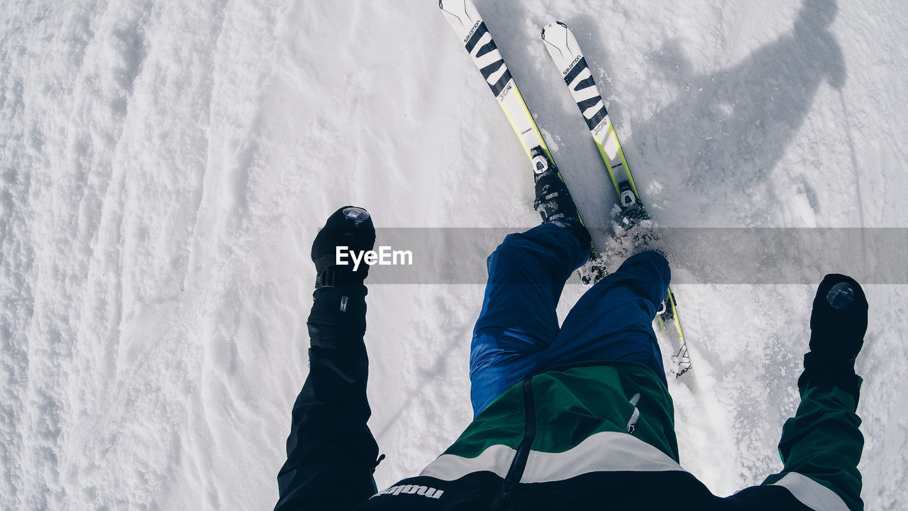 winter, cold temperature, snow, real people, one person, lifestyles, leisure activity, day, sport, nature, unrecognizable person, skiing, low section, high angle view, white color, winter sport, men, standing, outdoors, warm clothing, arms raised, ski-wear