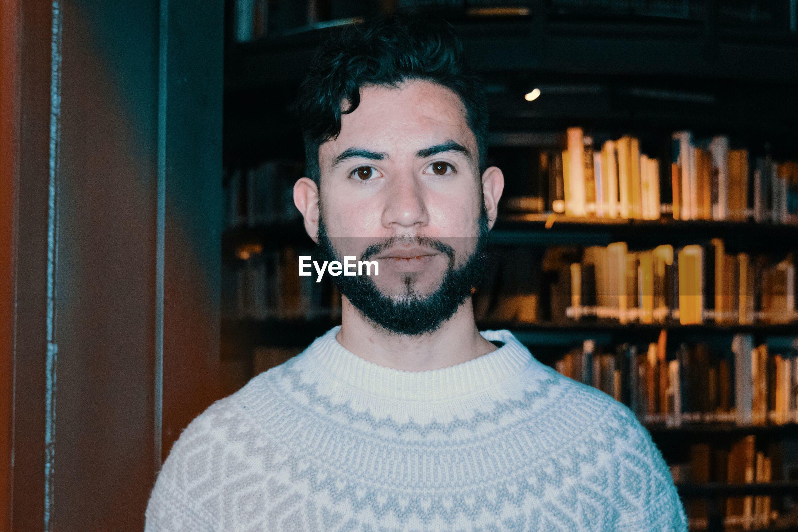 Portrait of young man against bookshelf