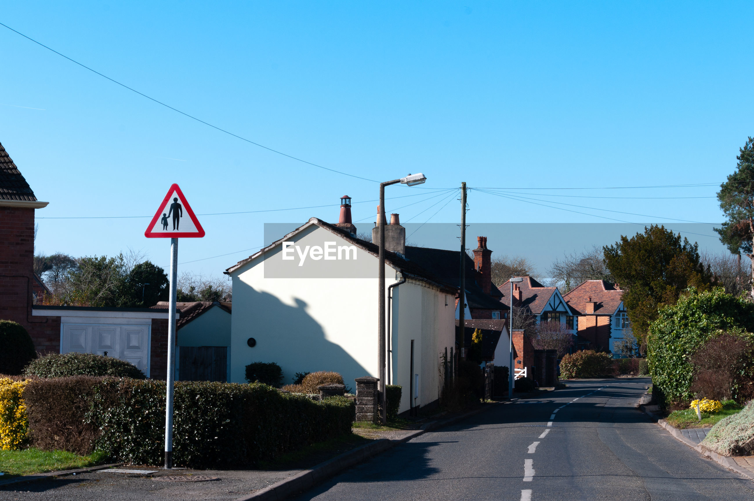 ROAD AMIDST HOUSES AGAINST CLEAR BLUE SKY