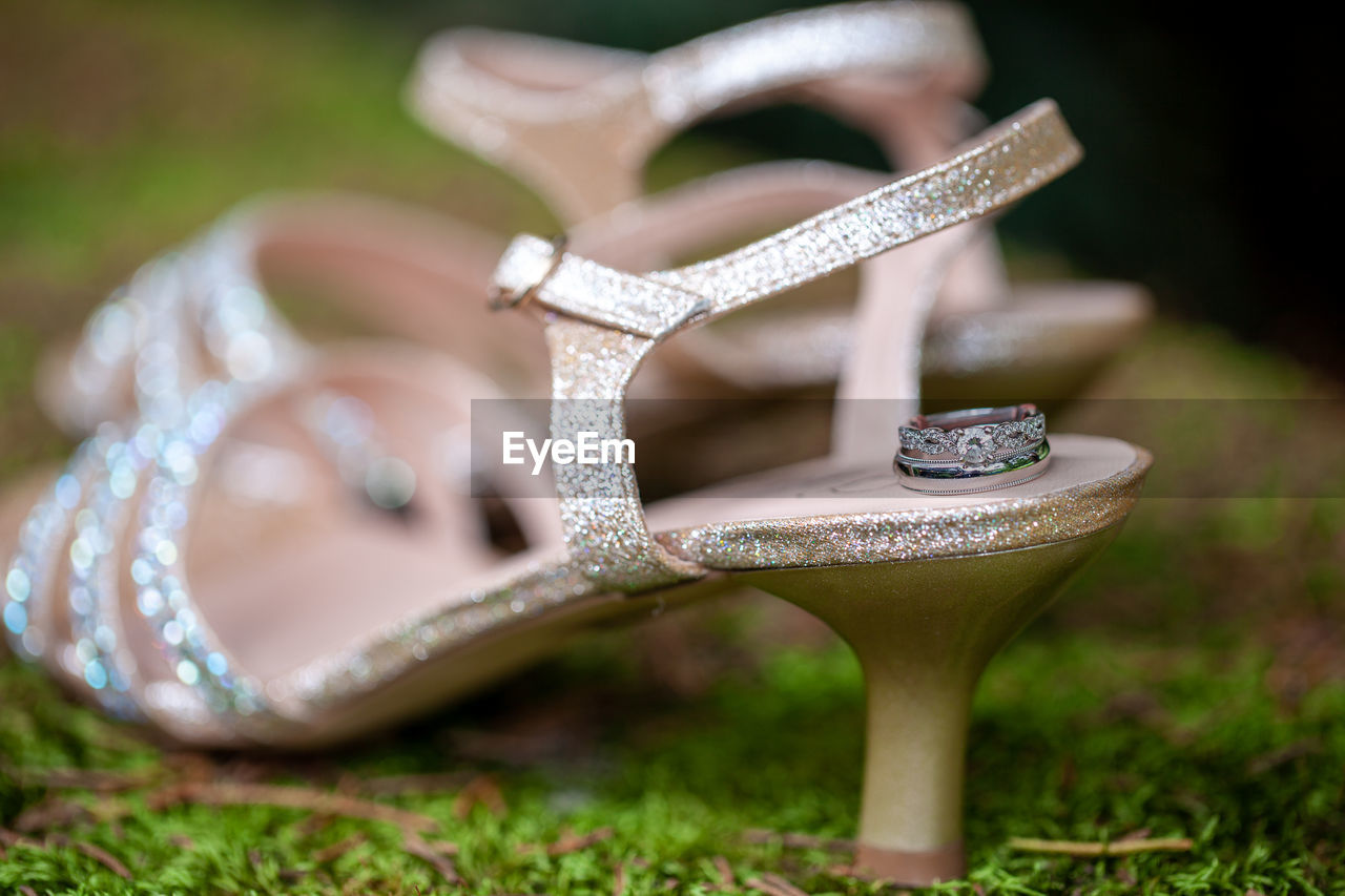 focus on foreground, no people, grass, selective focus, close-up, day, nature, plant, land, still life, field, outdoors, metal, art and craft, shoe, man made, wood - material, seat, man made object, work tool, silver colored