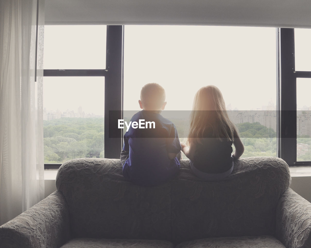 Rear View Of Siblings Looking Through Window While Sitting On Sofa At Home