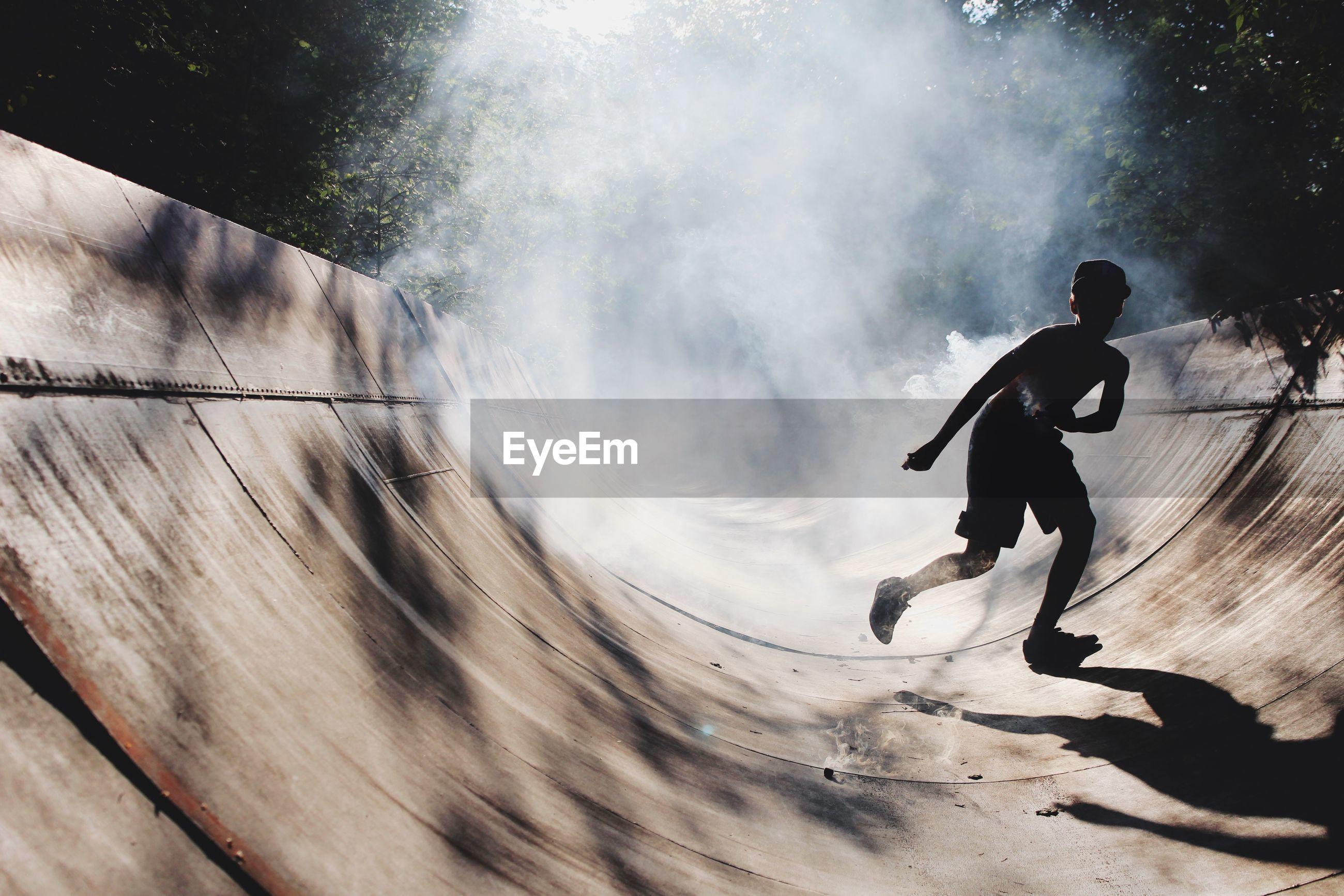 Teenage boy running on skateboard park during foggy weather