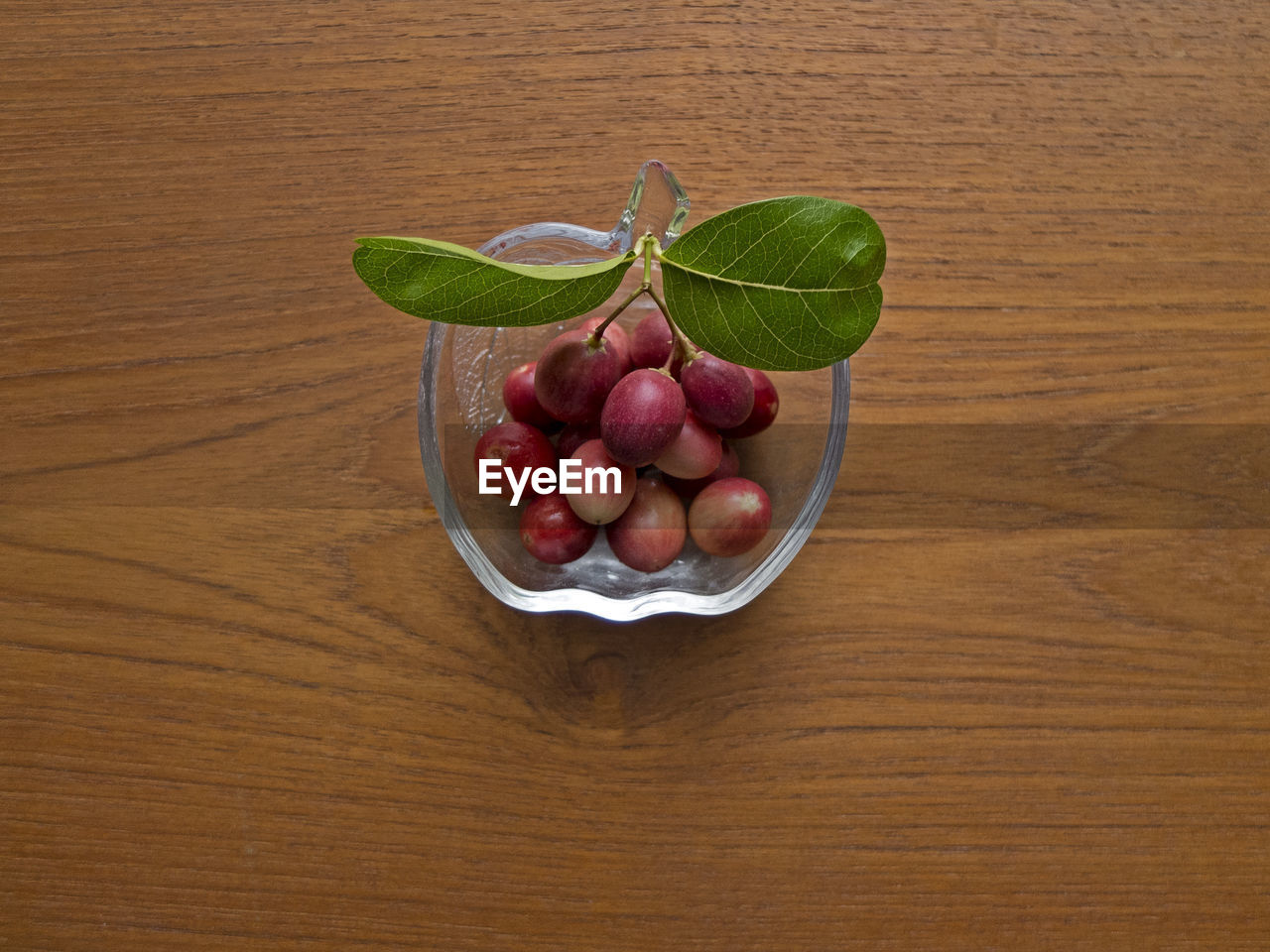 healthy eating, food, food and drink, wellbeing, table, wood - material, freshness, fruit, directly above, bowl, no people, indoors, high angle view, leaf, plant part, red, still life, organic, plate, green color, ripe, wood grain
