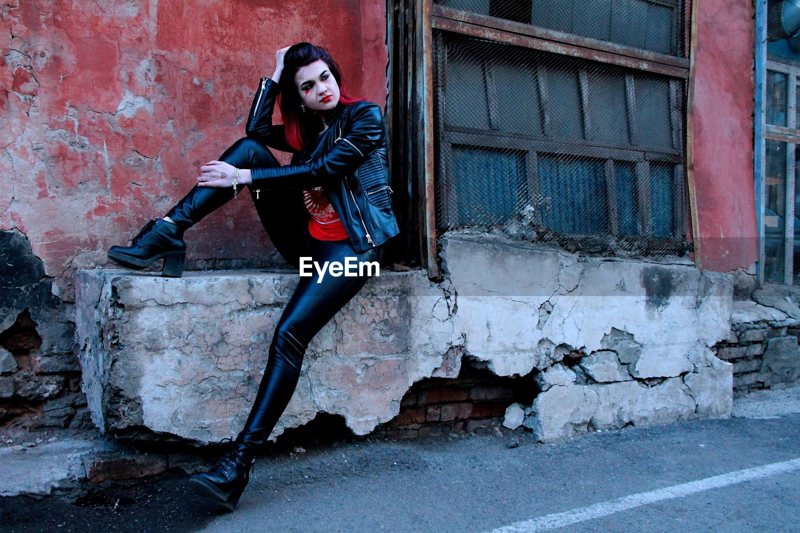 Portrait of punk woman by abandoned building