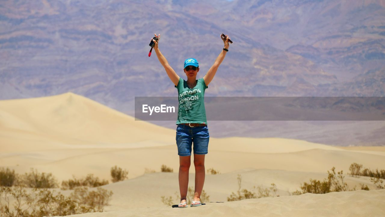 Arms Raised Young Woman Standing At Death Valley