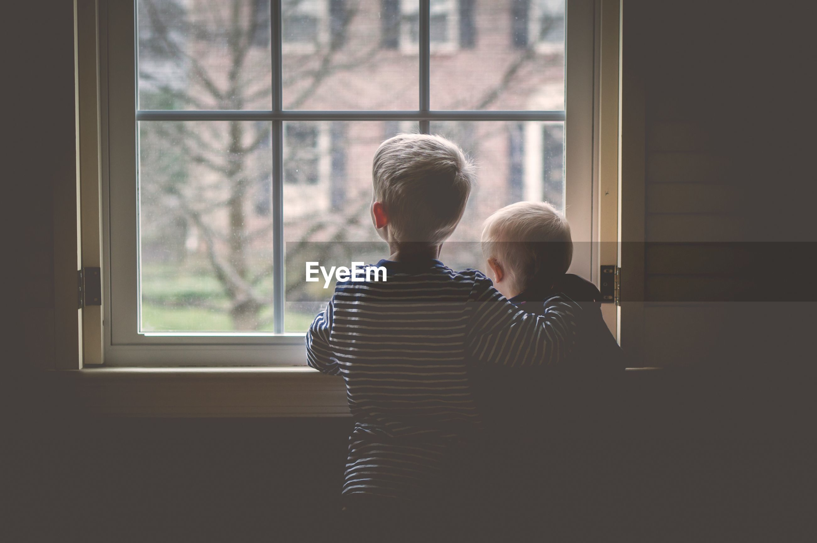 Two brothers looking through window