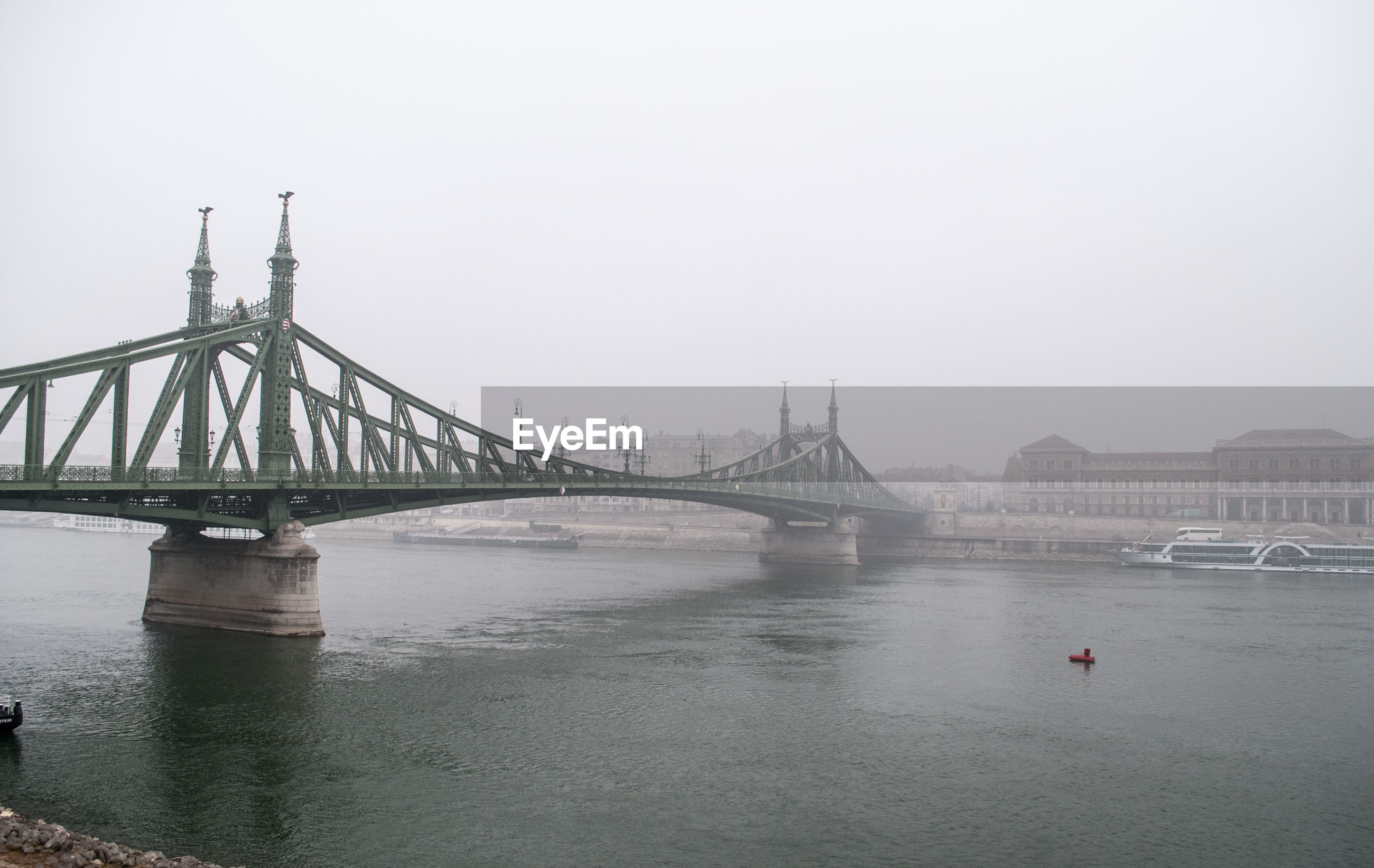Liberty bridge over danube river against sky