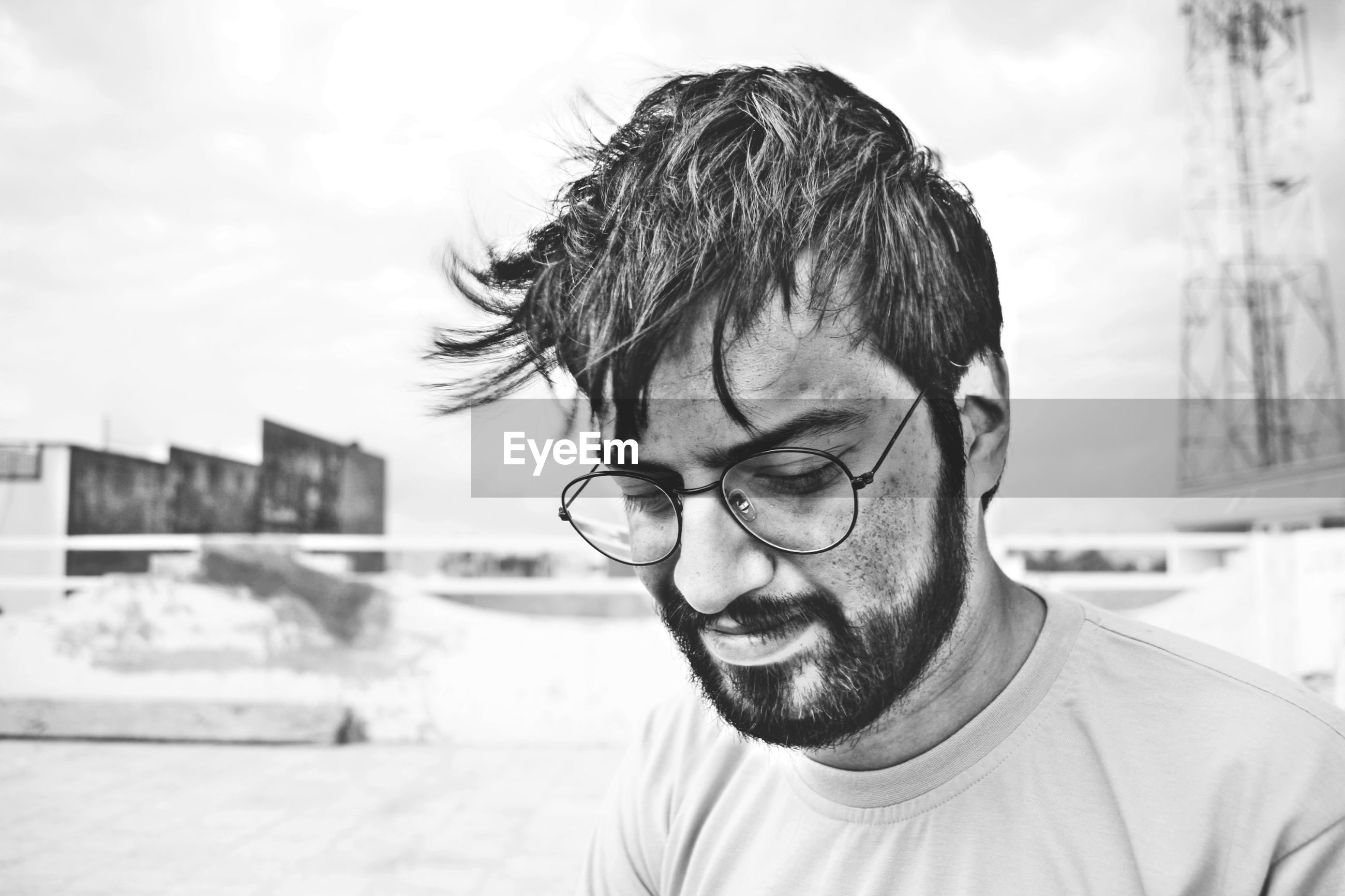 Close-up of bearded man wearing eyeglasses while looking down