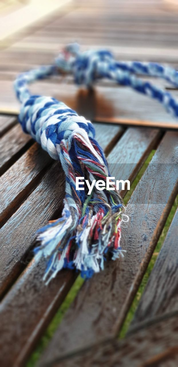 wood - material, selective focus, close-up, textile, no people, still life, blue, rope, multi colored, wool, table, indoors, art and craft, pattern, clothing, day, craft, high angle view, thread
