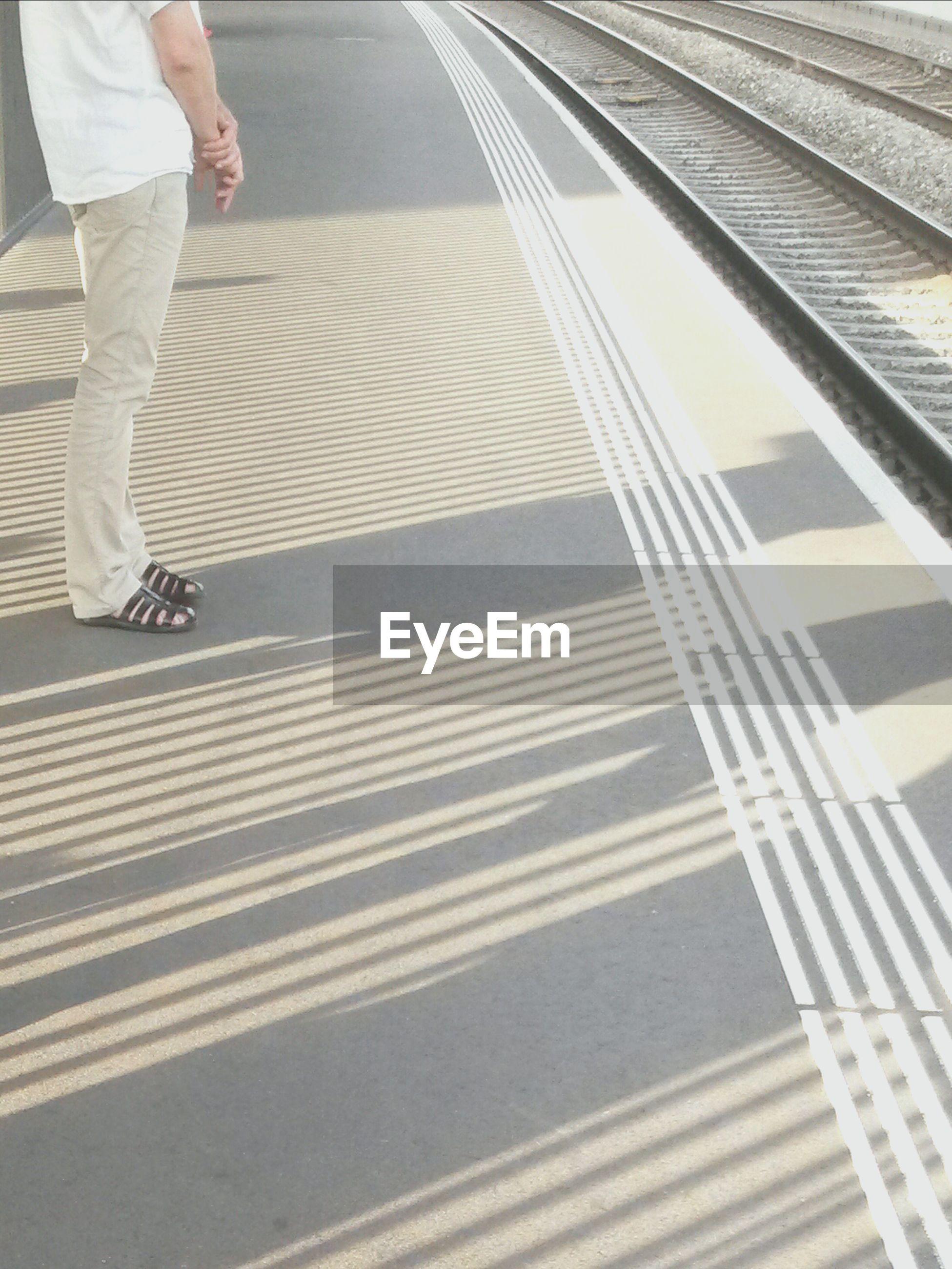 LOW SECTION OF MAN WALKING ON ASPHALT