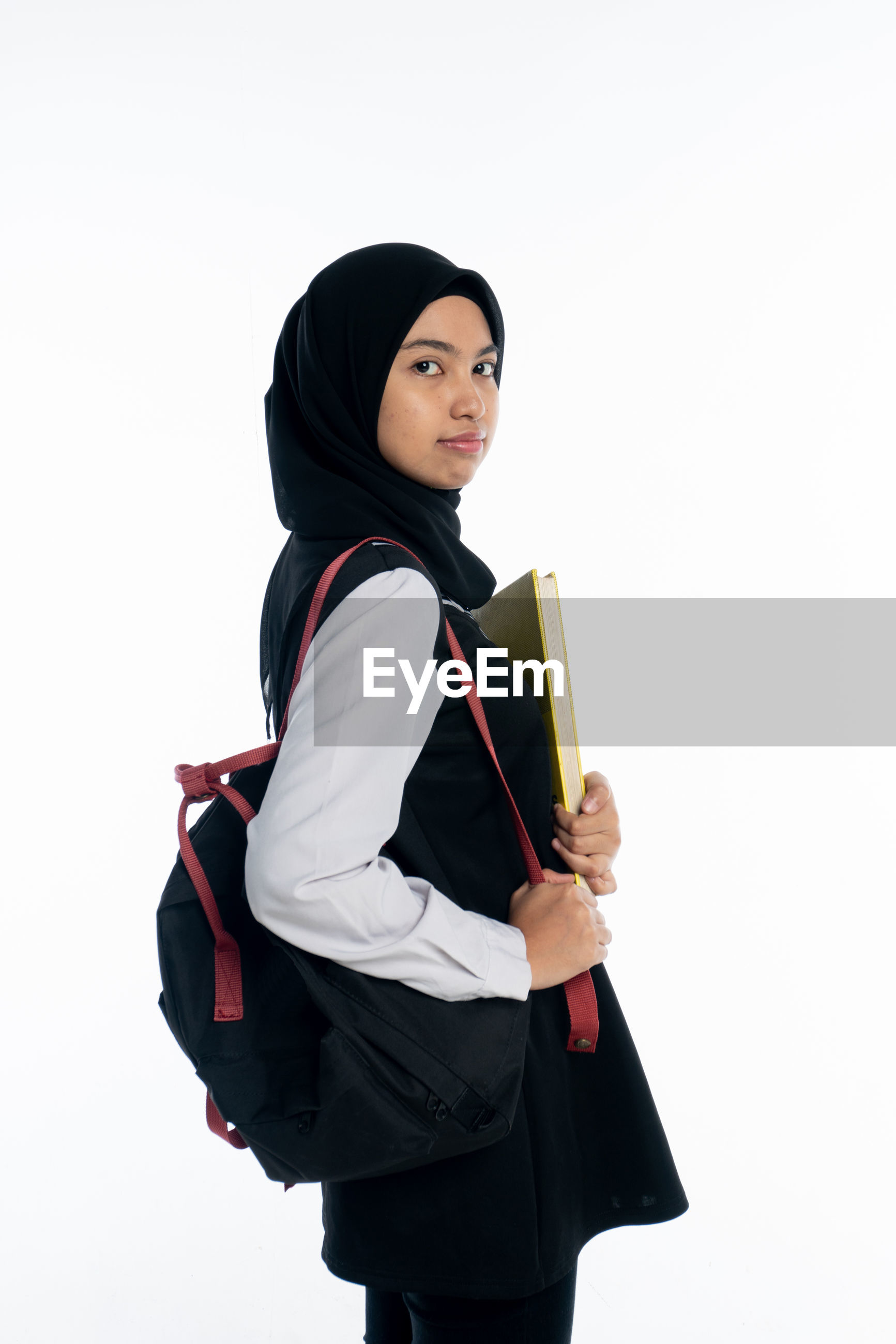 Portrait of young woman with backpack and book standing against white background